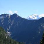 Near the top of ridgeline, Glacier Peak rises above the opposite mountains.
