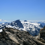 Cairn on top of Mt. Hinman, Summit Chief and Mt. Rainier visible...
